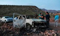 """CORRECTION - Members of the Lebaron family watch the burned car where part of the nine murdered members of the family were killed and burned during an gunmen ambush on Bavispe, Sonora mountains, Mexico, on November 5, 2019. - US President Donald Trump offered Tuesday to help Mexico """"wage war"""" on its cartels after three women and six children from an American Mormon community were murdered in an area notorious for drug traffickers. (Photo by Herika MARTINEZ / AFP) / """"The erroneous mention[s] appearing in the metadata of this photo by Herika MARTINEZ has been modified in AFP systems in the following manner: [AFP PHOTO / Herika MARTINEZ ] instead of [AFP PHOTO / STR ]. Please immediately remove the erroneous mention[s] from all your online services and delete it (them) from your servers. If you have been authorized by AFP to distribute it (them) to third parties, please ensure that the same actions are carried out by them. Failure to promptly comply with these instructions will entail liability on your part for any continued or post notification usage. Therefore we thank you very much for all your attention and prompt action. We are sorry for the inconvenience this notification may cause and remain at your disposal for any further information you may require."""""""
