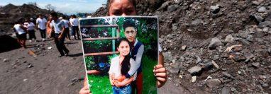 Una mujer sostiene la foto de unos familiares que murieron por la erupción del Volcán de Fuego el 3 de junio de 2018 en el primer aniversario de la tragedia en San Miguel Los Lotes, Guatemala.