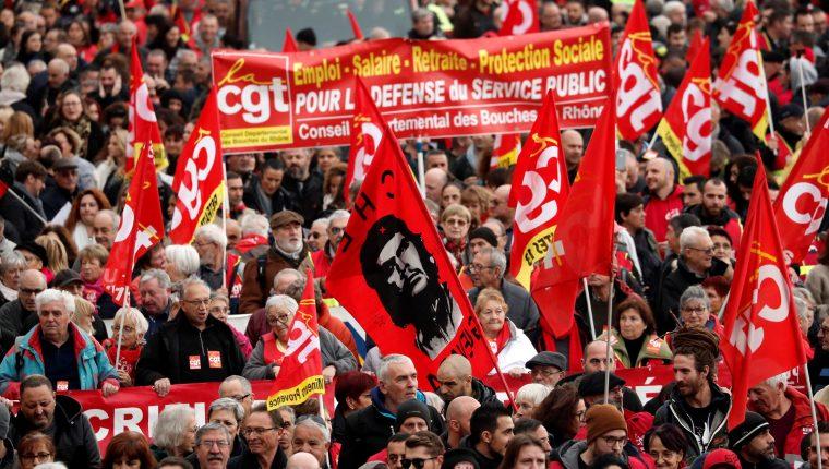 Empleados de empresas públicas y privadas sostienen pancartas durante una manifestación en el marco de la huelga general francesa contra la reforma de las pensiones. (Foto Prensa Libre: EFE)