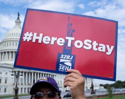 """Fotografía de archivo del 9 de septiembre de 2019 donde aparece una persona mientras sostiene un cartel que dice """"Aquí para quedarnos"""", durante una manifestación de inmigrantes enfrente del Capitolio en Washington. (Foto Prensa Libre: EFE)"""