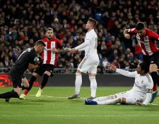 El portero del Athletic de Bilbao Unai Simón (i) detiene un balón ante Luka Jovic (c) y Sergio Ramos durante el partido de Liga en el estadio Santiago Bernabéu. (Foto Prensa Libre: EFE).