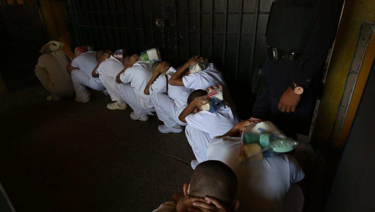Un grupo de reos espera su llamado para ser trasladados a nuevos centros penitenciarios en el Centro Penal de Seguridad de Chalatenango en El Salvador. (Foto Prensa Libre: EFE)