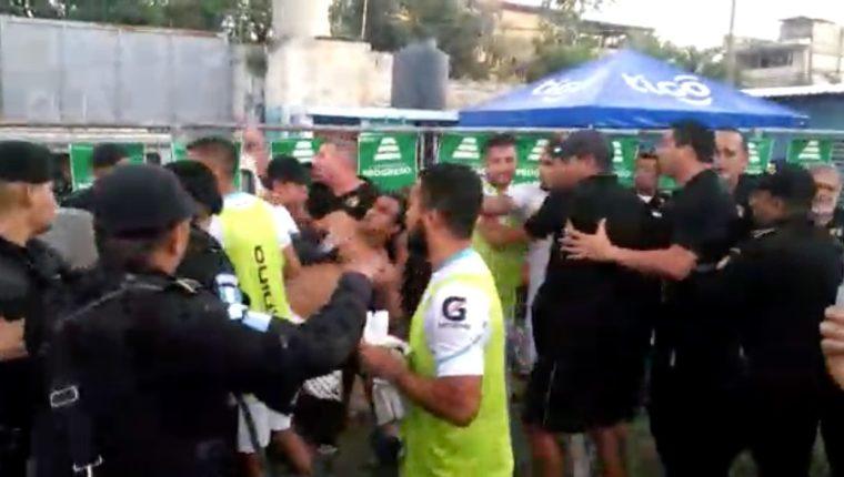 El mediocampista Fredy Thompson es detenido por sus compañeros en la discusión con las fuerzas de seguridad. (Foto Prensa Libre: video)
