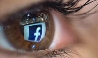 """(FILES) In this file photo taken on March 22, 2018 An illustration picture taken on March 22, 2018 in Paris shows a close-up of the Facebook logo in the eye of an AFP collaborator posing while she looks at a flipped logo of Facebook. - Facebook, under pressure to ramp up privacy rules across its platform, said on August 20, 2019 it was rolling out a tool allowing users to control data that it receives from other apps and websites about their online activity. The new tool is to give clients access to their so-called """"off-Facebook activity"""" -- fed back to Facebook with the aim of targeting advertisements -- and give them the option of deleting it. (Photo by Christophe SIMON / AFP)"""