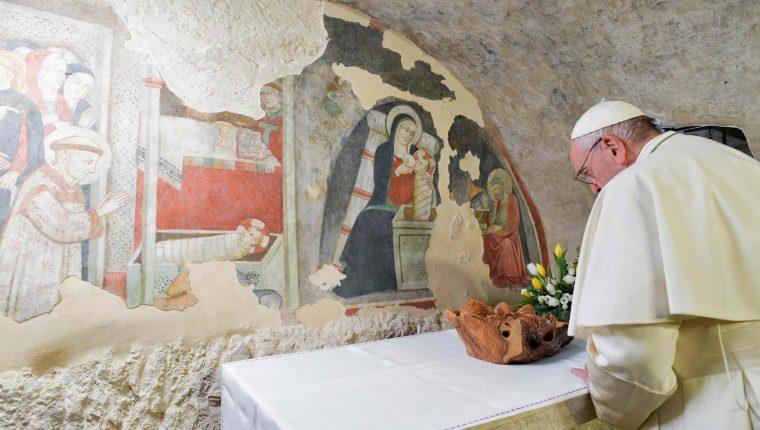 El papa Francisco ora frente a los frescos de la Natividad en la ciudad de el Greccio. Foto Prensa Libre AFP