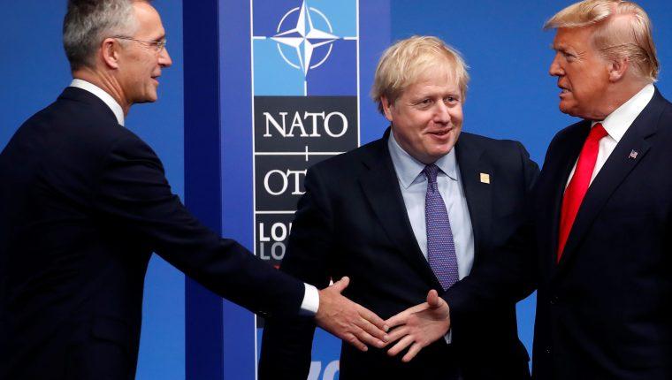El presidente de los Estados Unidos Donald Trump se saluda con el secretario general de la OTAN Jens Stoltenberg, en medio el primer ministro británico Boris Johnson. (Foto Prensa Libre: AFP)