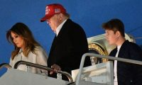 "(FILES) In this file photo taken on December 1, 2019, US President Donald Trump, First Lady Melania Trump and son Barron step off Air Force One upon arrival at Andrews Air Force Base, Maryland. - Melania Trump on December 4, 2019, publicly rebuked Constitutional law professor Pamela Karlan,who used her 13-year-old son's name to make a point during an impeachment hearing against the president. Karlan invoked Barron Trump to demonstrate how the Constitution imposes distinctions between a monarch's power and that of a president. ""The constitution says there can be no titles of nobility,"" Karlan told lawmakers, ""So while the president can name his son 'Barron', he can't make him a baron."" The pun led to chuckles in the congressional hearing room, but Melania Trump made clear it was no laughing matter. (Photo by MANDEL NGAN / AFP)"