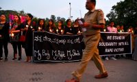 A policeman walks past as people hold a candlelight vigil in support of sexual assault victims and against the alleged rape and murder of a 27-year-old veterinary doctor in Hyderabad, in Bangalore on December 6, 2019. - Indian police on December 6 shot dead four detained gang-rape and murder suspects as they were re-enacting their alleged crime, prompting celebrations but also accusations of extrajudicial killings. (Photo by Manjunath Kiran / AFP)