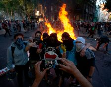 Demonstrators pose for a picture near a bonfire at a blocked street during a protest against the government of Chilean President Sebastian Pinera, in Santiago, on December 06, 2019. - Thusands protested in Santiago Friday after 50 days of social crisis -the worst in 30 years-, which has downturned local economy. (Photo by CLAUDIO REYES / AFP)