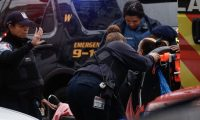 A woman receives medical assistance on the scene where active shooting is happening in Jersey City on December 10, 2019. - One officer was shot when two gunmen with a long rifle opened fire in Jersey City, New Jersey, on the afternoon of December 10, 2019 , according to two officials. Two suspects were barricaded in a convenience store, the officials said. One officer was being taken to a nearby hospital. (Photo by Kena Betancur / AFP)