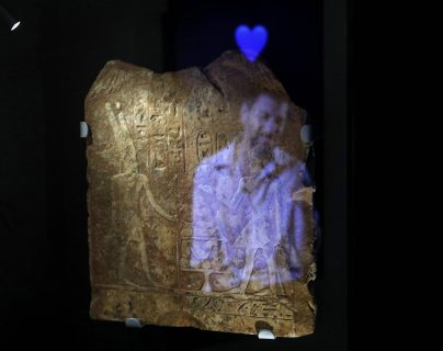 Una instalación de vídeo muestra la imagen de un hombre con el emoji de un corazón azul reflejado en una placa egipcia antigua grabada con jeroglíficos, parte del concepto de esta exposición en Israel.  (Foto Prensa Libre:  MENAHEM KAHANA / AFP)