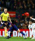 El delantero argentino del FC Barcelona Leo Messi (c) cae entre el brasileño Casemiro (i) y el uruguayo Fede Valverde. (Foto Prensa Libre: EFE)
