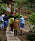 La enfermera Laura Sánchez (derecha) camina con un grupo de portadores de VIH en el refugio Casa Zulema en Honduras. (Foto Prensa Libre: AFP)