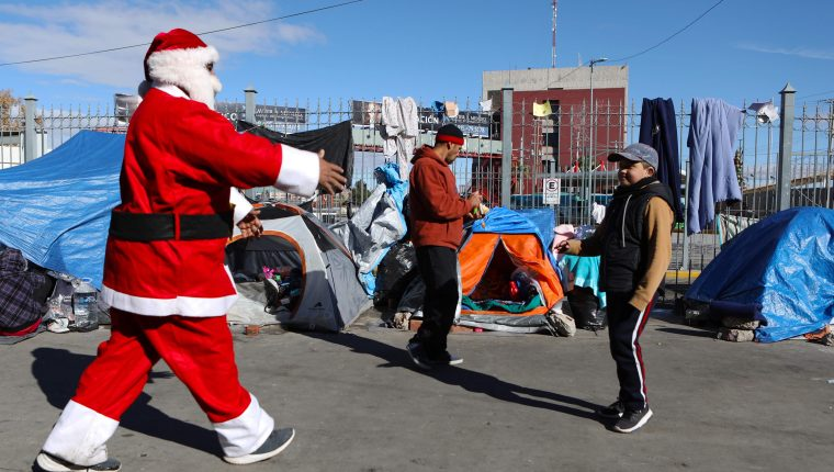 Santa saluda a un niño migrante en Ciudad Juárez. (Foto Prensa Libre: AFP)