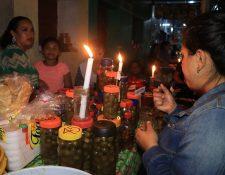 Una mujer preuba uno de los dulces que frecen familias de San Francisco en las tradicionales mesitas, las cuales marcan el inicio de la temporada navideña en Petén. (Foto Prensa Libre: Dony Stewart)