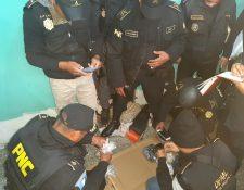 Investigadores y policías revisan los objetos decomisados en la Granja Cantel, Quetzaltenango. (Foto Prensa Libre: PNC)