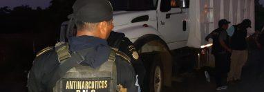 Un agente antinarcóticos custodia el camión donde era transportada la droga. (Foto Prensa Libre: PNC)