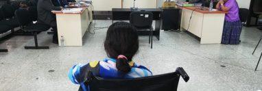 Angelina Coy Choc, una de las detenidas, en silla de ruedas, observa a los abogados, la jueza y fiscales durante la audiencia. (Foto Prensa Libre: Edwin Pitán)