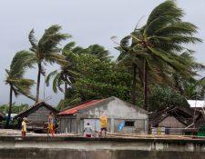 Los aldeanos ven fuertes vientos que soplan árboles junto a las casas en la ciudad de Calabanga, provincia de Camarines sur, Filipinas. (Foto Prensa Libre: EFE)