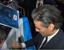 Entre ovaciones, gritos y aplausos, Oscar Isaac firma la bandera de Guatemala.