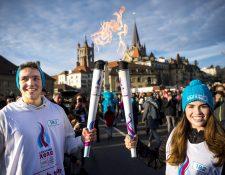 Los jóvenes atletas sostienen la Llama Olímpica de los Juegos Olímpicos de la Juventud de Invierno de Lausana 2020 frente a la catedral de Lausana, Suiza. (Foto Prensa Libre: EFE)