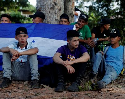 Migrantes hondureños esperan en Morales, Izabal luego de que la Policía Nacional Civil los bajara de los autobuses en los que se movían en caravana rumbo a Estados Unidos. (Foto Prensa Libre: EFE)