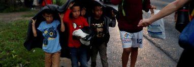 Un grupo de niños que hace parte de la caravana de migrantes hondureños se cubre de la lluvia mientras recorrían una carretera en Chiquimula. (Foto Prensa Libre: EFE)