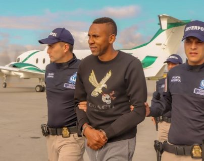 Fotografía cedida por la Policía de Colombia que muestra el momento en el que agentes de la Interpol trasladan al exfubolista internacional Jhon Viáfara (c) a un avión para su extradición hacia EE.UU. (Foto Prensa Libre: EFE)