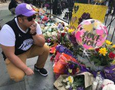 El guatemalteco Eddy Ascencio, de 24 años coloca flores en los altares improvisados para Kobe Bryant, a las afueras del Staples Center. (Foto Prensa Libre: EFE)