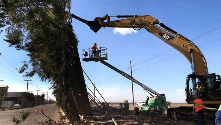 Fotografía cedida por Rafael Torres donde se muestra a una grúa mientras intenta sostener trozos del muro fronterizo que cayeron este miércoles en la frontera de Calexico, California. (Foto Prensa Libre: EFE)