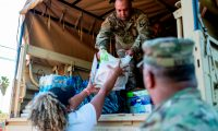 A Puerto Rico National Guard gives supplies to a resident in Guanica, Puerto Rico on January 11, 2020, after a powerful earthquake hit the island. - A 5.9 magnitude earthquake rocked Puerto Rico Saturday, the latest in a series of powerful tremors that have shaken the US territory in recent days, the US Geological Survey reported. The latest quake occurred at 8:54 am local time (1254 GMT) around 13 kilometers (eight miles) southeast of Guanica, a town on the island's southern Caribbean coastline that was hard hit by earlier quakes. (Photo by Ricardo ARDUENGO / AFP)