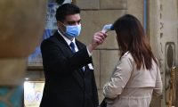 A staff member checks the temperature of a guest entering the New Orient Landmark hotel in Macau on January 22, 2020, after the former Portuguese colony reported its first case of the new SARS-like virus that originated from Wuhan in China. - Macau on January 22 reported its first confirmed case of the new SARS-like coronavirus as authorities announced all staff in the city's bustling casinos had been ordered to wear face masks. (Photo by Anthony WALLACE / AFP)