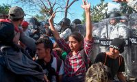 Members of the Mexican National Guard scuffle with Central American migrants - mostly Hondurans heading in a caravan to the US - in Ciudad Hidalgo, Chiapas State, Mexico, on January 23, 2020. - Hundreds of Central American migrants surged into Mexico Thursday, wading unopposed across a river on the Guatemalan border where Mexican troops had used tear gas earlier in the week to keep them back, AFP journalists at the scene reported. (Photo by ALFREDO ESTRELLA / AFP)