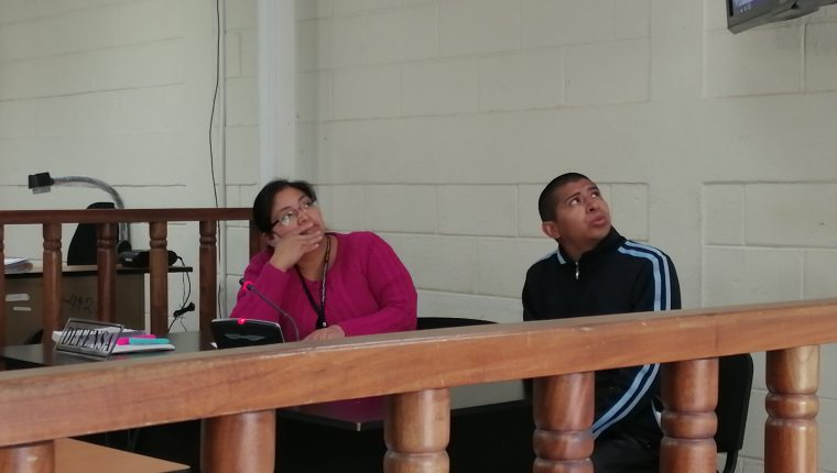 Melvin Quijivix y su abogada defensora observan las fotografías de las heridas que tenía la víctima. (Foto Prensa Libre: María Longo)