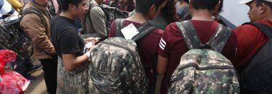 Deportados, en las afueras de la Fuerza Aérea, avenida Hincapié, zona 13, tratan de ponerse de acuerdo para retirarse del lugar. (Foto Prensa Libre: Esbin García)