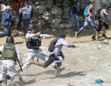 Policías mexicanos intentan detener a un migrante que cruza hacia México en la frontera con Guatemala. (Foto Prensa Libre: AFP).