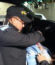 Un policía resguarda al bebé encontrado en un autobús en Chimaltenango. (Foto Prensa Libre: Cortesía)