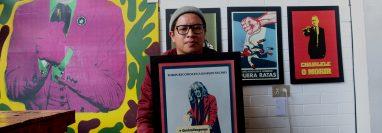 Santiago Lucah sostiene el arte de Pedro Tirapiedras y está rodeado por las otras obras. (Foto Prensa Libre: María Longo)