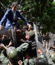 El líder opositor Juan Guaidó trepa una reja en un intento por ingresar a la sede de la Asamblea Nacional, custodiada por la policía para impedir su ingreso. (Foto Prensa Libre: EFE)