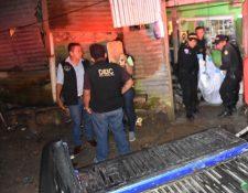 Agentes de la PNC retiran de la vivienda el cadáver de Carlos Humberto Santos Ramos, quien murió baleado en Izabal. (Foto Prensa Libre: Dony Stewart).