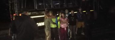 Migrantes hondureños junto a unos de los buses que los trajo desde la frontera con México. (Foto Prensa Libre: Conred).