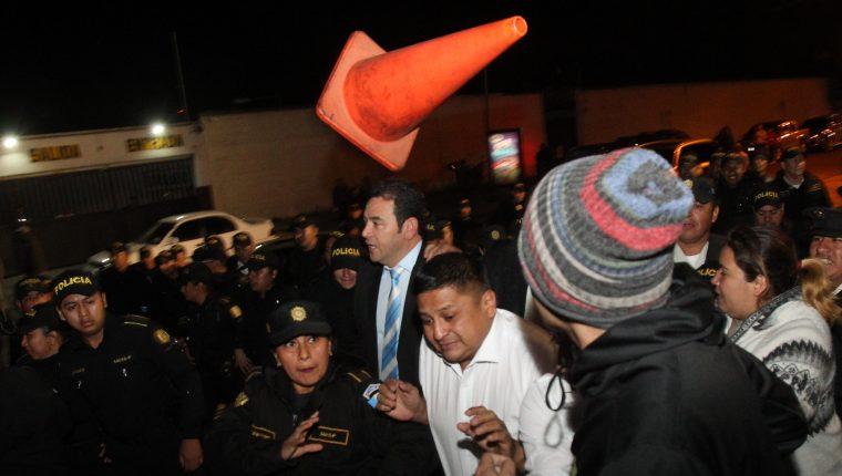 Momento en que, en medio de una protesta ciudadana, Jimmy Morales intenta sin éxito ingresar a un hotel para ser juramentado como diputado al Parlacén. (Foto Prensa Libre: EFE)