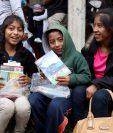Dos niños junto a su madre sonríen luego de recibir una bolsa con útiles escolares donados por familiares del veterano de guerra, Domingo Tomás. (Foto Prensa Libre. Mike Castillo)