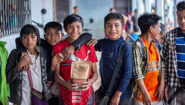 Un grupo de niños de Guaisná, San Mateo Ixtatán, sostienen una de las bolsas de café cuyas ganancias pagan el salario de los maestros que este año imparten clases en el básico. (Foto Prensa Libre: Mike Castillo)
