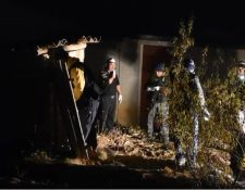 Un fiscal de Ministerio Público revisa el interior de la letrina donde estaba el cadáver. (Foto Prensa Libre: Leopoldo Batz)