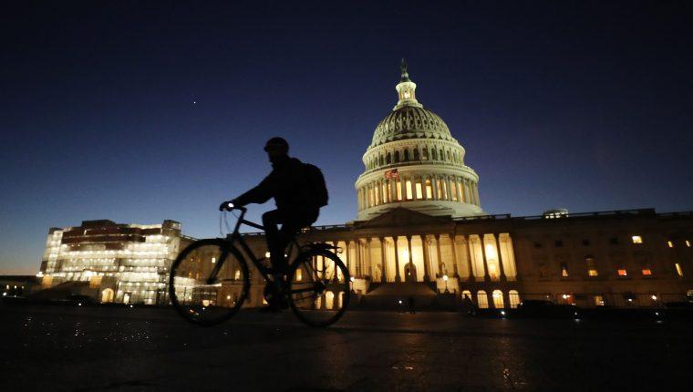 Un ciclista pasa frente al Capitolio durante el comienzo del juicio político contra Trump. (Foto Prensa Libre: AFP)