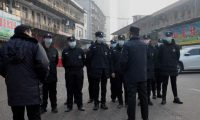 (FILES) In this file photograph taken on January 11, 2020 security guards stand in front of the closed Huanan wholesale seafood market, where health authorities say a man who died from a respiratory illness had purchased goods from, in the city of Wuhan, Hubei province. - A second person has died in China from a mystery virus that has stricken dozens and appeared in two other Asian countries, officials said. (Photo by NOEL CELIS / AFP)