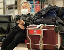 Los viajeros deben protegerse con boquilla para evitar contagio. (Foto Prensa Libre: EFE)