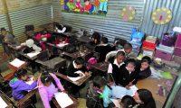 Alumnos de la Escuela Plan Grande, Municipio de Palencia,  acuden a su primer dia de clases  luego que  las autoridades del Ministerio de Educación inauguran el Ciclo Escolar 2014, Los niños que va a estudiar en la  precariedad, hacinamiento y la falta de la construcción de una parte  de la escuela,  pues el aula  estan  construidas  de laminas, mientras el resto esta en una salon. Fotografia Esbin Garcia