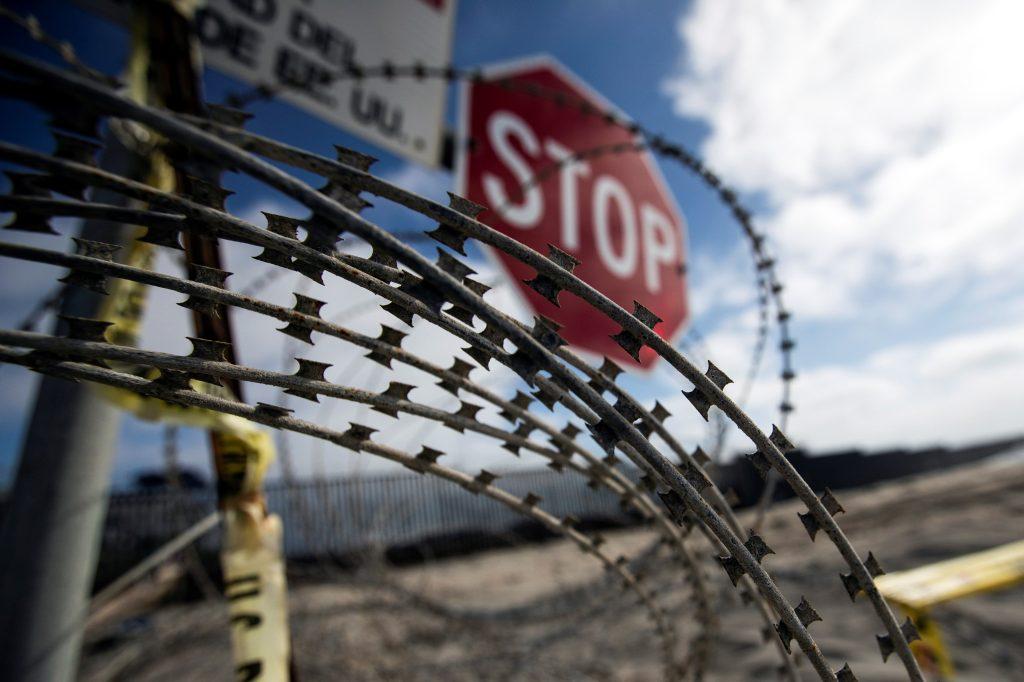 Los alambres y letreros prohíben la entrada a una zona restringida donde el muro que delimita la frontera entre EE.UU.